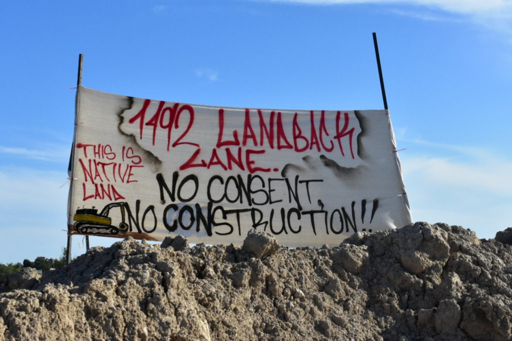 Spandoek met de tekst 1492 Lanaback Lane. No Consent No construction!! This is native land. Op het spandoek is een gele graafmachine getekend