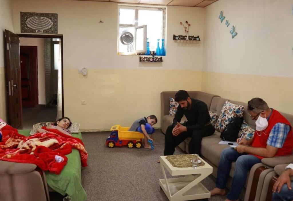 Een kamer waarin Peiman Talib op een bed ligt. Een kind speelt met een speelgoedauto en twee mannen zitten op de bank.