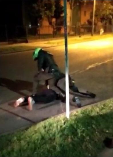 Een agent werkt een arrestant gewelddadig tegen de grond